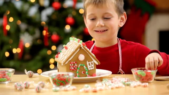 junger mann dekorieren ein gingerbread house für weihnachten - lebkuchenhaus stock-videos und b-roll-filmmaterial