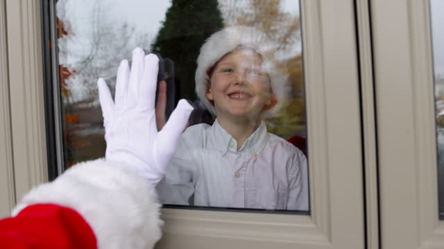 giovane ragazzo facendo high-five con babbo natale attraverso la finestra di casa durante covid-19 pandemico - hand on glass covid video stock e b–roll
