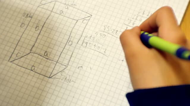 stockvideo's en b-roll-footage met jonge jongen doet zijn harde school huiswerk zittend op het bureau - schooljongen