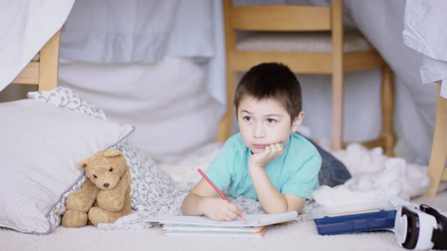 vidéos et rushes de jeune garçon à faire ses devoirs en fort fait de feuilles - forteresse
