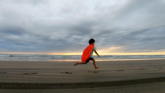 ung pojke klädd som en super hjälte kör på stranden - superhjälte isolated bildbanksvideor och videomaterial från bakom kulisserna