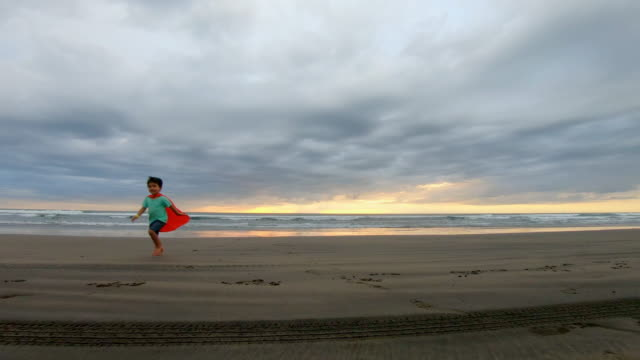 Young Boy Dressed as a Super Hero Running on the Beach video