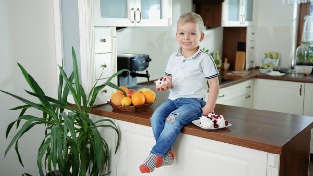Ein kleiner Junge, der Kuchen in der Küche isst – Video