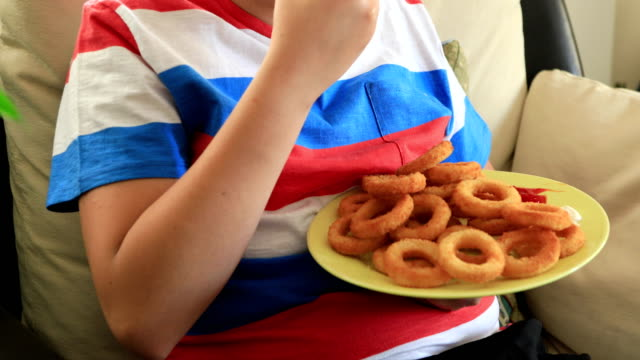 young boy eating onion rings - sovrappeso video stock e b–roll