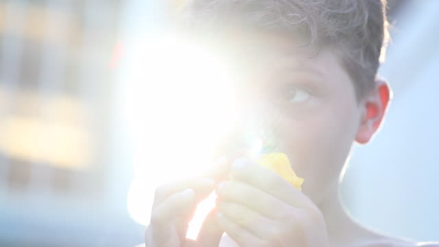 young boy eating peach outside in the sunlight lens-flare. child taking a bite of healthy snack fruit outdoors - pesche bambino video stock e b–roll