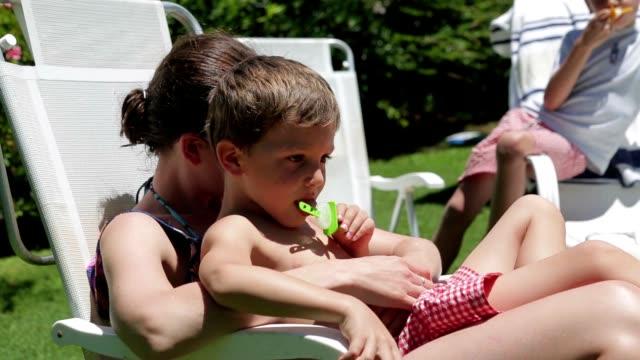 giovane ragazzo che mangia ghiacciolo mentre perde nel pensiero. bambino tra le braccia della madre mentre è seduto all'aperto - dorso umano video stock e b–roll