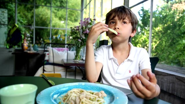 Young boy eating spaghetti. Child eating lunch. Young boy eating carbs at outdoor balcony video