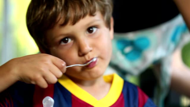 Young boy eating yogurt with spoon. 6 year old kid eating supper desert video