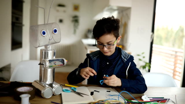 Young boy engineer constructing a robot at home One boy, making a robot from recycled materials, working on creative homework at home. one boy only stock videos & royalty-free footage