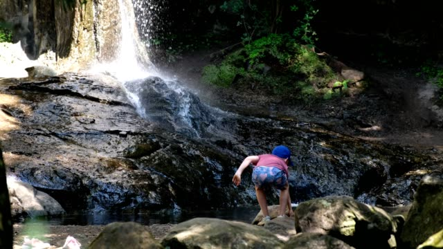 Young boy enjoys playing at the rock pool by the waterfall