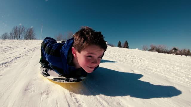 il ragazzo si diverte a slittino sulla neve - slitta video stock e b–roll