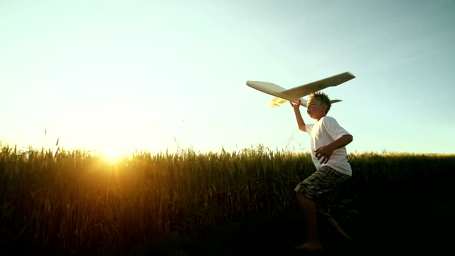 Young boy flys an airplane in the country