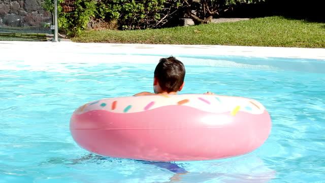 vídeos de stock e filmes b-roll de young boy getting on top of pink float at swimming pool - brinquedos na piscina