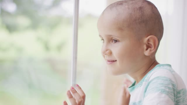 Young Boy Going Through Cancer Treatments A young boy smiles as he looks out of a winder. The boy has hair loss due to cancer treatments cancer illness stock videos & royalty-free footage