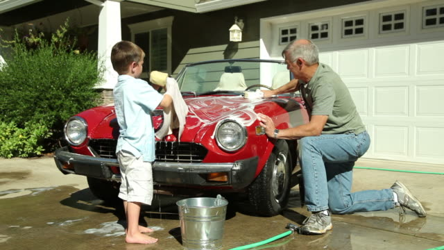 Young boy helps Grandfather wash car  chores stock videos & royalty-free footage