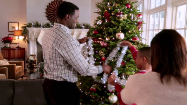 Young boy helps mom and dad string tinsel on Christmas tree Young boy helps mom and dad string tinsel on Christmas tree christmas decoration stock videos & royalty-free footage