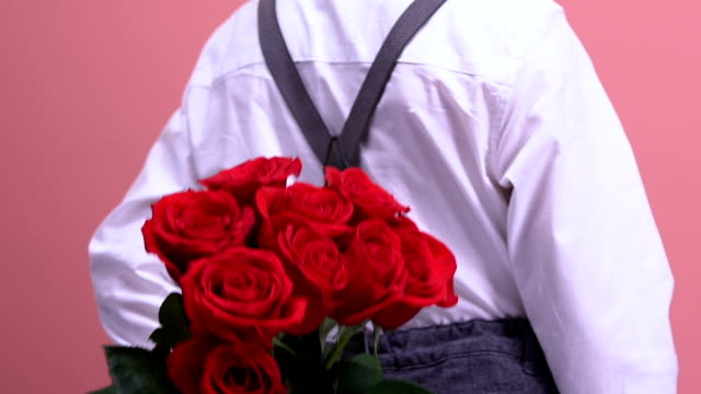 Young boy hiding roses behind back and presenting to little girl, first love Young boy hiding roses behind back and presenting to little girl, first love back to back stock videos & royalty-free footage