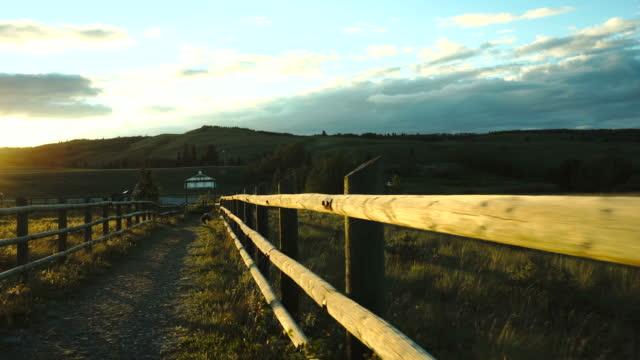 young boy hikes along path towards rural church - solo bambini maschi video stock e b–roll