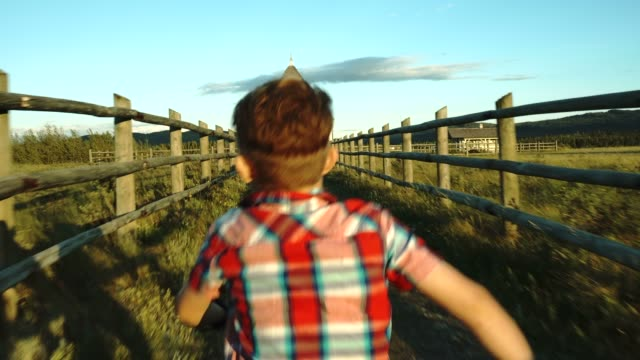 Young boy hikes along path towards rural church