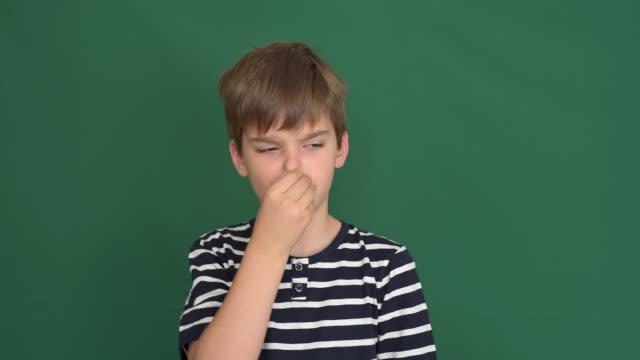 vídeos de stock e filmes b-roll de young boy holding his nose with his fingers on the green screen - cheiro desagradável