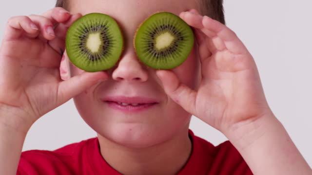 young boy holding kiwi fruit over eyes - kiwifrukt bildbanksvideor och videomaterial från bakom kulisserna