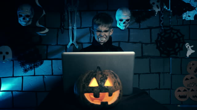 Young boy in a vampire costume for Halloween showing his scary people over the internet Young boy in a vampire costume for Halloween showing his scary people over the internet count dracula stock videos & royalty-free footage