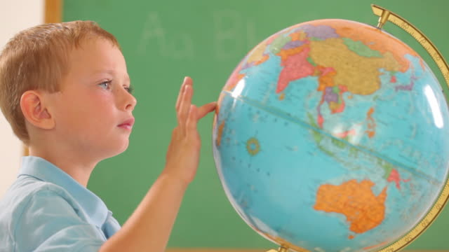 stockvideo's en b-roll-footage met young boy in classroom looking at globe - bureauglobe