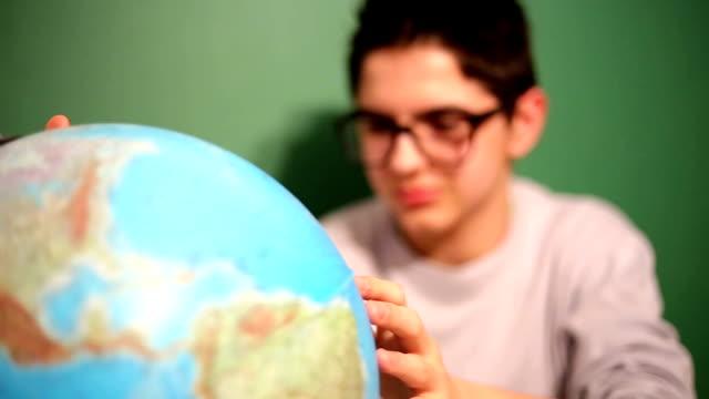 ung pojke i klassrummet tittar på globen - bordsjordglob bildbanksvideor och videomaterial från bakom kulisserna