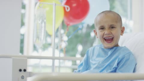 Young Boy in Hospital Laughing A young boy is wearing a hospital gown and laying in a hospital bed. He has Cancer. He is laughing and smiling. There are some balloons in the background childhood stock videos & royalty-free footage