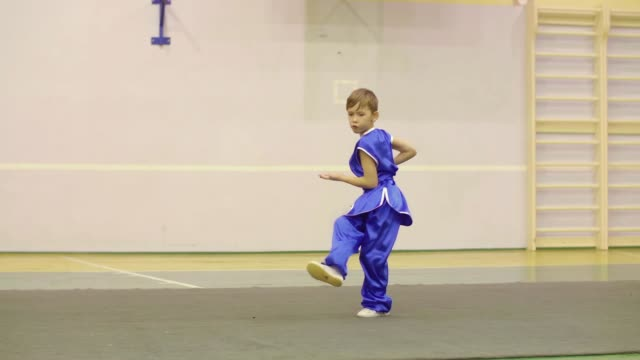 Young boy in national Chinese dress is practicing Kung Fu wushu tai chi Nanquan form