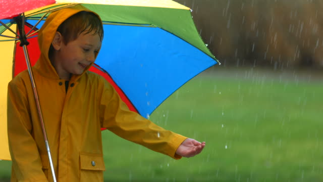 Young boy in rain with umbrella, slow motion video
