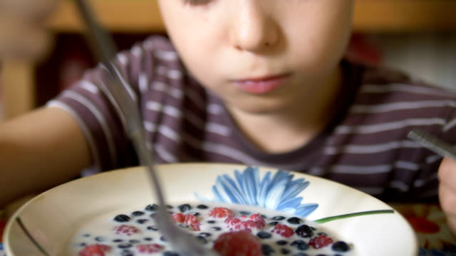 young boy in striped t-shirt eats fresh delicious berries