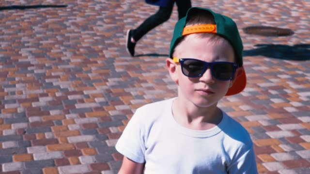 young boy in sunglasses and a cap walking down the street, child 6 year old kid walking, slow motion - pesche bambino video stock e b–roll