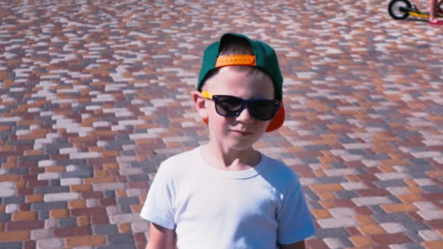 Young boy in sunglasses and a cap walking down the street, Child 6 year old kid walking, slow motion Young boy in sunglasses and a cap walking down the street, Child 6 year old kid walking, slow motion, close-up one boy only stock videos & royalty-free footage
