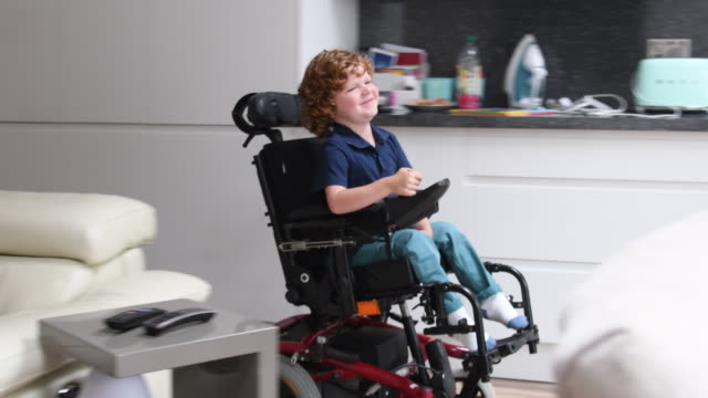Young boy in wheelchair approaching camera talking and smiling Boy with muscular dystrophy controlling electric wheelchair, entering kitchen and heading towards table with digital tablet wheelchair stock videos & royalty-free footage