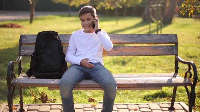 Young boy in white sweatshirt with black backpack sitting on the bench in the park and speak with somebody by the phone Young boy in white sweatshirt with black backpack sitting on the bench in the park and speak with somebody by the phone. sweatshirt stock videos & royalty-free footage