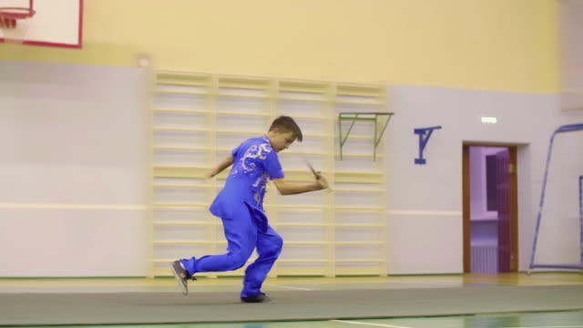 Young boy in yifu chinese clothing for martial arts training wushu exercises