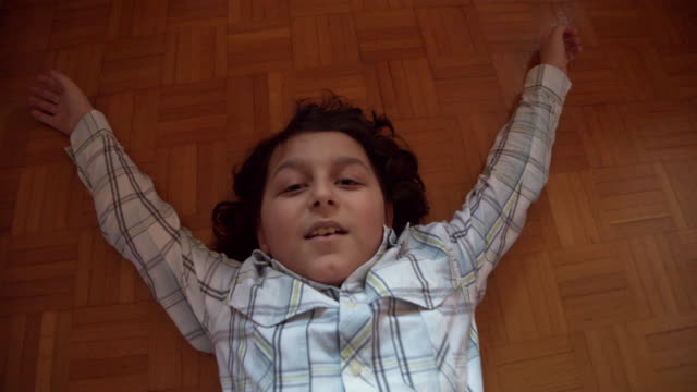 Young boy is lying down on the floor, looking at camera - Slow motion video video