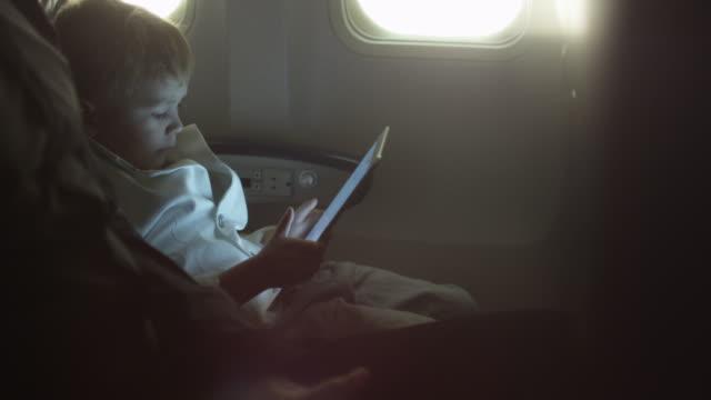 kleiner junge spielt mit dem tablet in einem flugzeug neben einem fenster. - tablet mit displayinhalt stock-videos und b-roll-filmmaterial