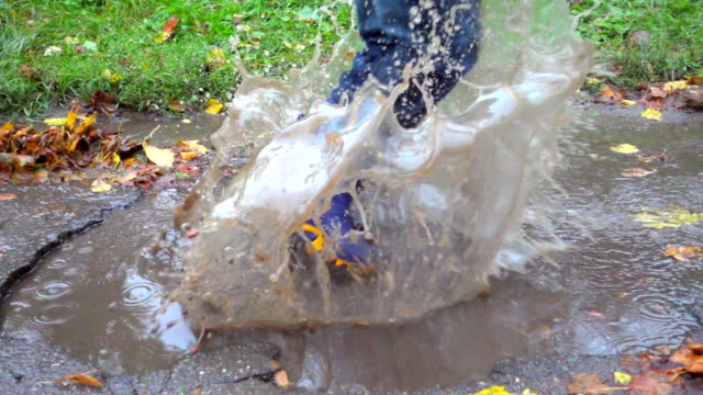 vídeos de stock e filmes b-roll de young boy jumping in muddy puddle, slow motion - bota
