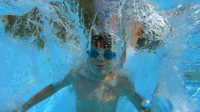 genç çocuk açık havuza atlama. eylem yavaş vurdu - yüzmek stok videoları ve detay görüntü çekimi
