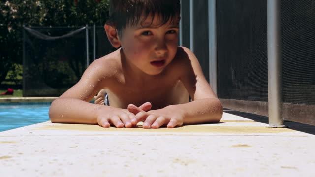 молодой мальчик лежал, а для принятия солнечных ванн у бассейна - vitamin d стоковые видео и кадры b-roll