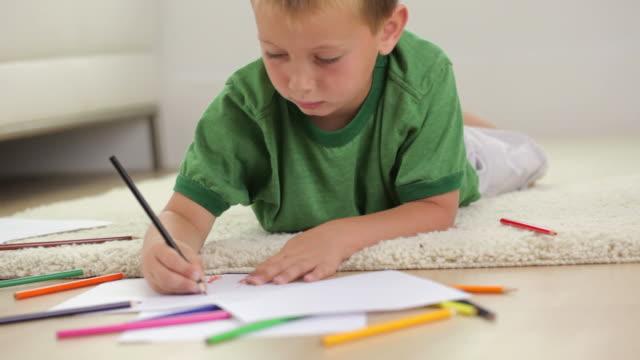 giovane ragazzo sdraiato lavorando su un progetto di arte - tappeto video stock e b–roll
