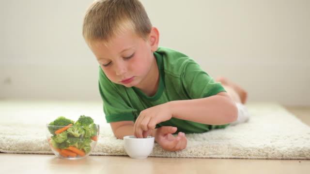 giovane ragazzo posa sul tappeto mangia carote e broccoli - broccolo video stock e b–roll
