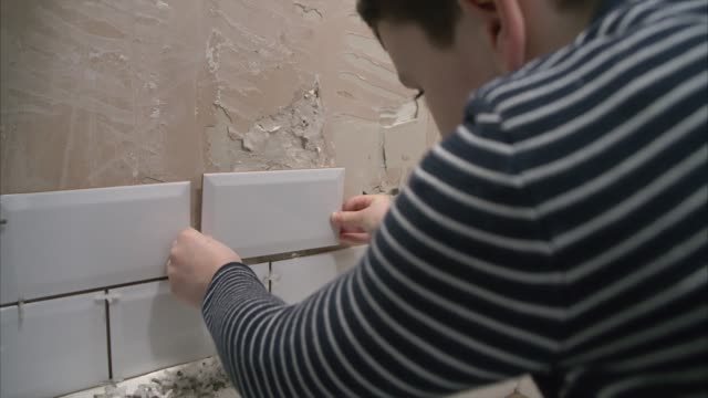 Young boy learning home improvement skills off his dad