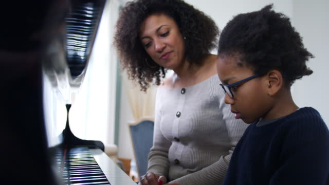 vídeos de stock e filmes b-roll de young boy learning to play piano having lesson from female teacher - piano