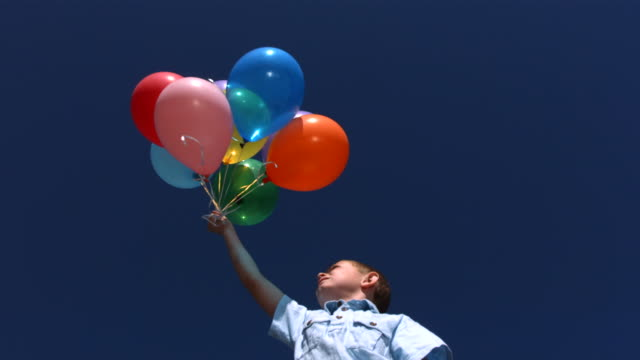 Young boy lets balloons go into sky, slow motion video