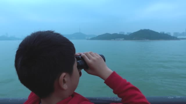 Young boy looking around with binoculars on tourboat