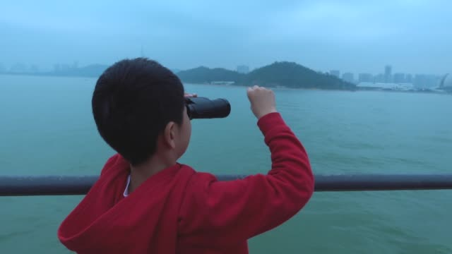Young boy looking cityscape with binoculars on tourboat