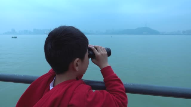 Young boy looking with binoculars on tourboat